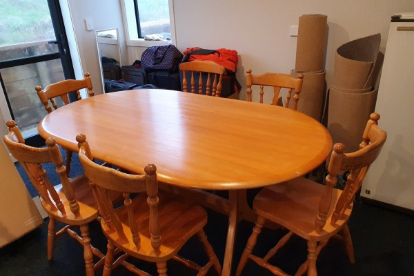 Table and six chairs, The table has a glass top fully wrapped.